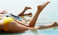 Image of row of bottoms of friends lying in water Stock Photo - Royalty-Freenull, Code: 400-06077830