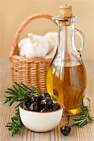 Olive oil, black olives and fresh garlic in a basket. Stock Photo - Royalty-Freenull, Code: 400-06079348