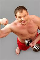Smiling guy working out and looking at camera, isolated on grey background, the above view Stock Photo - Royalty-Freenull, Code: 400-06083765