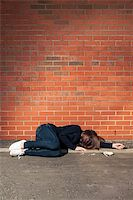 Addicted, sad young woman lying against the brick wall with syringe and cigarettes beside. Vertical. Stock Photo - Royalty-Freenull, Code: 400-06100323