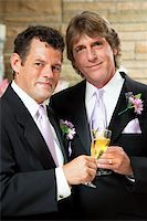 Handsome gay couple give champagne toast at their wedding reception. Stock Photo - Royalty-Freenull, Code: 400-06100742
