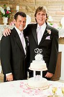 Handsome gay couple at their wedding reception, getting ready to cut the cake. Stock Photo - Royalty-Freenull, Code: 400-06100750
