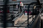 Biker doing double peg grind down the hand rail over the stairs Stock Photo - Royalty-Free, Artist: dmitryelagin                  , Code: 400-06101518