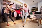 Image of two greedy girls fighting for red tanktop in department store Stock Photo - Royalty-Free, Artist: pressmaster                   , Code: 400-06104203