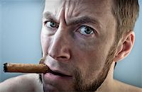 a man with a cigar, looking into the camera Stock Photo - Royalty-Freenull, Code: 400-06106720