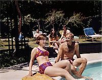 1960s FOUR PEOPLE ON PATIO COUPLE MAN WOMAN SITTING ON EDGE OF SWIMMING POOL Stock Photo - Premium Rights-Managednull, Code: 846-06111764