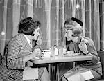 1960s TWO WOMEN GOSSIPING AT LUNCH IN RESTAURANT
