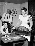 1950s MOCK TURN OF THE 20TH CENTURY THANKSGIVING DINNER SMILING MOTHER SHOWING ROAST TURKEY TO PLEASED HUSBAND AND SURPRISED SON