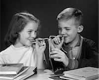 1960s BOY AND GIRL SHARING SINGLE BOTTLE OF SODA WITH TWO STRAWS AT TABLE WITH BOOKS INSIDE Stock Photo - Premium Rights-Managednull, Code: 846-06111791