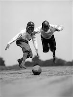 1930s PAIR OF BOYS IN KNICKERS & LEATHER HELMETS RACING TO DIVE ON FOOTBALL Stock Photo - Premium Rights-Managednull, Code: 846-06111798