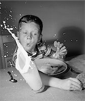 1960s BOY HAVING LUNCH KNOCKING OVER MILK REACHING FOR COOKIE SURPRISE SPLASH INDOOR Stock Photo - Premium Rights-Managednull, Code: 846-06111800