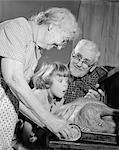 1950s 1960s EXCITED LITTLE GIRL GRANDDAUGHTER WITH GRANDPARENTS WATCHING ROAST TURKEY COMING OUT OF OVEN