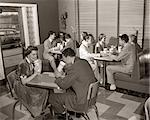 1950s MALT SHOP INTERIOR WITH TEENS AT BOOTHS DRINKING FROM DIXIE CUPS