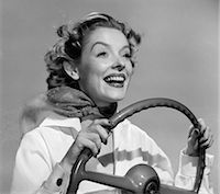 right - 1950s SMILING WOMAN WITH HANDS ON STEERING WHEEL WITH WIND BLOWING BACK HAIR & SCARF STUDIO OUTDOOR Stock Photo - Premium Rights-Managednull, Code: 846-06111816