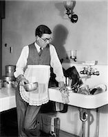 release - 1920s MAN IN APRON LEANING ON SINK FULL OF DIRTY DISHES RAG IN ONE HAND POT IN OTHER Stock Photo - Premium Rights-Managednull, Code: 846-06111875
