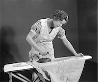1930s TIRED WOMAN HOUSEWIFE WEARING APRON IRONING SHIRT WITH ELECTRIC IRON ON IRONING BOARD Stock Photo - Premium Rights-Managednull, Code: 846-06111890