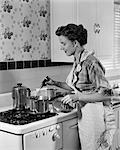 1950s HOUSEWIFE IN APRON STIRRING FOOD IN SAUCEPAN ON STOVE