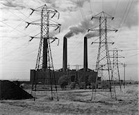 1950s INDUSTRIAL POWER PLANT BILLOWING SMOKE TO GENERATE ELECTRICITY POWER LINE TOWERS IN FOREGROUND Stock Photo - Premium Rights-Managednull, Code: 846-06111902