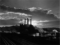 1930s SUNRISE SUNSET BEHIND SILHOUETTE OF INDUSTRIAL POWER PLANT WITH SMOKE STACKS NEAR RIVER Stock Photo - Premium Rights-Managednull, Code: 846-06111904