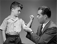 1940s BOY MAKES MUSCLE FOR MAN FATHER Stock Photo - Premium Rights-Managednull, Code: 846-06111917