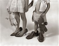 1950s 1960s CLOSE-UP OF LITTLE GIRL & BOY FROM NECK DOWN WEARING PARENTS' SHOES Stock Photo - Premium Rights-Managednull, Code: 846-06111921