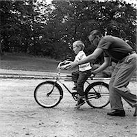 release - 1960s FATHER GIVING SON ON BIKE A PUSH TEACHING HIM HOW TO RIDE BICYCLE Stock Photo - Premium Rights-Managednull, Code: 846-06111923