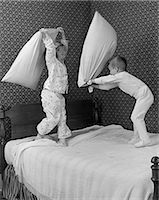 1950s BOY & GIRL BROTHER & SISTER IN PAJAMAS HAVING PILLOW FIGHT ON BED Stock Photo - Premium Rights-Managednull, Code: 846-06111938