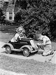 1940s 1930s BOY ON SIDEWALK FIXING HEADLIGHT OF TOY CAR DRIVEN BY LITTLE GIRL PLAYING OUTDOOR Stock Photo - Premium Rights-Managed, Artist: ClassicStock, Code: 846-06111943