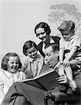 1930s FAMILY OF FIVE GROUPED AROUND FATHER READING CHILDREN'S PUNCH BOOK
