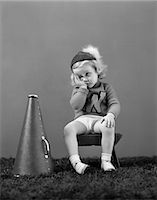 right - 1940s UNHAPPY LITTLE GIRL CHEERLEADER WEARING A CAP AND VARSITY SWEATER FRUSTRATED SAD LOOK Stock Photo - Premium Rights-Managednull, Code: 846-06111958