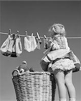 1950s BACK VIEW OF GIRL HANGING LAUNDRY WIND BLOWING SKIRT TO SHOW RUFFLED PANTIES Stock Photo - Premium Rights-Managednull, Code: 846-06111975