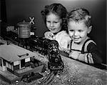 1950s BOY & GIRL STANDING AT TABLE WATCHING TOY TRAIN GOING AROUND TRACK