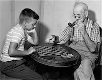 1950s BOY PLAYING CHECKERS WITH GRANDFATHER SMOKING PIPE & PICKING UP PIECE TO JUMP HIS CHECKER Stock Photo - Premium Rights-Managednull, Code: 846-06111992