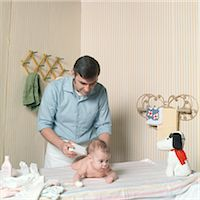 1970s FATHER CHANGING BABY GIRL DIAPER POWDERING BUTT Stock Photo - Premium Rights-Managednull, Code: 846-06112032