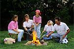 1990s FAMILY ROASTING HOT DOGS ON STICKS OVER CAMPFIRE
