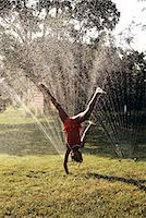 LITTLE GIRL CARTWHEELING THROUGH LAWN SPRINKLER Stock Photo - Premium Rights-Managednull, Code: 846-06112076