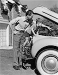 1940s FATHER & SON CHECKING UNDER HOOD OF CAR IN DRIVEWAY