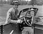1930s 1940s PORTRAIT COUPLE MAN WOMAN TOGETHER WITH CONVERTIBLE AUTOMOBILE SMILING WEARING HATS LOOKING AT CAMERA