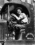 1940s TRUCK DRIVER LOOKING AT CAMERA IN WORK SHIRT & HAT POSED BEHIND WHEEL OF TRUCK WITH OPEN SIDE NO DOOR