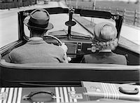 1930s 1940s REAR VIEW COUPLE DRIVING TOGETHER IN CONVERTIBLE  LUGGAGE IN BACK SEAT Stock Photo - Premium Rights-Managednull, Code: 846-06112149