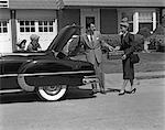 1950s HUSBAND AND WIFE PACKING TRUNK OF CONVERTIBLE WITH LUGGAGE WHILE SON & DAUGHTER WATCH FROM BACK SEAT