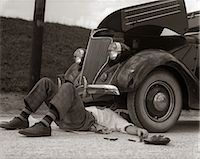 stalled car - 1930s MAN ON BACK WEARING STRIPED SOCKS FIXING CAR Stock Photo - Premium Rights-Managednull, Code: 846-06112175