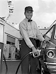 1960s MALE SERVICE STATION ATTENDANT WEARING CAP AND BOW TIE SMILING WHILE PUMPING GASOLINE OUTSIDE