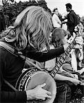 1970s SIDE VIEW OF HIPPIE TEEN OUTDOOR GATHERING WITH LONG-HAIRED BOY IN FOREGROUND PLAYING BANJO
