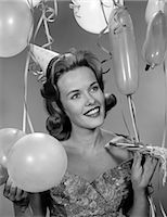 1960s 1950s WOMAN IN PARTY DRESS SMILING HOLDING BALLOON AND NOISE MAKER Stock Photo - Premium Rights-Managednull, Code: 846-06112205