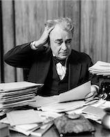person overwhelmed stresss - 1930s ELDERLY BUSINESSMAN SITTING AT DESK AMONG STACKS OF PAPERS WITH HAND IN HAIR & FLUSTERED EXPRESSION Stock Photo - Premium Rights-Managednull, Code: 846-06112222