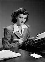 secretary desk - 1940s SERIOUS SECRETARY STENOGRAPHER WOMAN WITH PENCIL CHECKING NOTEPAD SITTING AT DESK WITH MANUAL TYPEWRITER LOOKING AT CAMERA Stock Photo - Premium Rights-Managednull, Code: 846-06112228