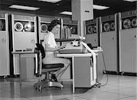 secretary desk - 1960s WOMAN IN MAINFRAME COMPUTER ROOM SURROUNDED BY MANY DATA TAPE DRIVES SITTING AT DESK TYPING ON TYPEWRITER INDOOR Stock Photo - Premium Rights-Managednull, Code: 846-06112229