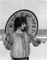 release - 1920s WOMAN STANDING ON BEACH HOLDING ORIENTAL UMBRELLA LOOKING OFF TO SIDE Stock Photo - Premium Rights-Managednull, Code: 846-06112236