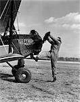 1920s MALE PILOT TRYING TO TURN PLANE'S PROPELLER BY HAND